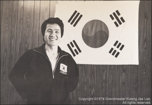 Grandmaster Lee smiles in front of a Korean flag