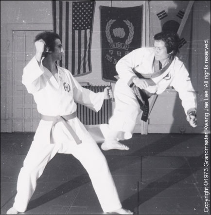 Grandmaster Lee demonstrates a forward scissor kick with student, Joe. —Bergenfield, NJ 1973